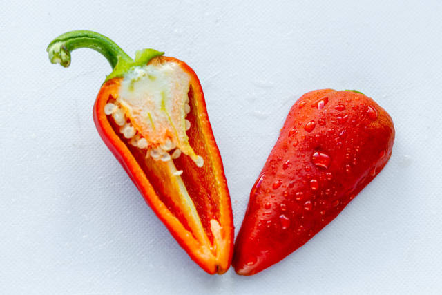 Cut red pepper halves on white background