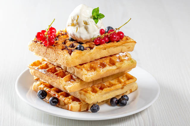 Stack of waffles with fresh berries and ice cream