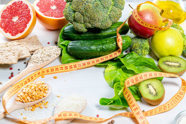Fresh fruits, vegetables and cereals with measuring tape. Weight loss concept