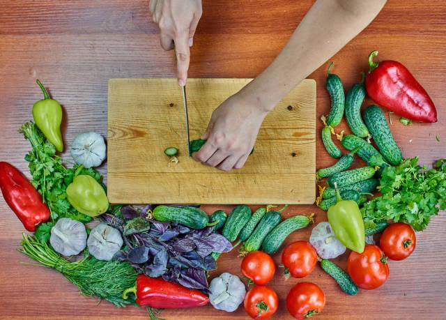 Woman preparing a healthy vegetarian salad with raw vegetables