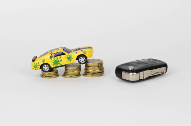 Spielzeugauto auf aufeinander gestapelten Münzen und Autoschlüssel
