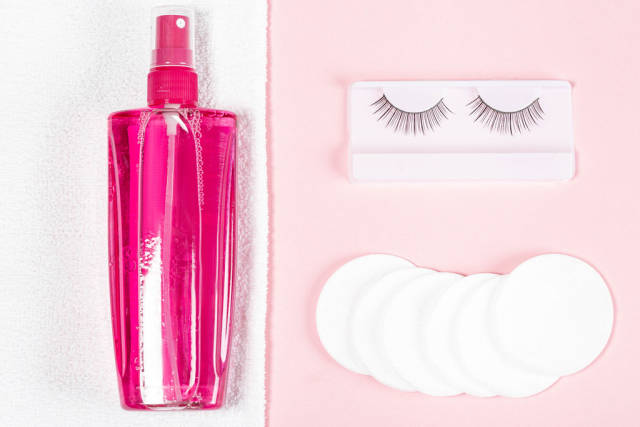 Makeup remover, white towel, cotton pads and false eyelashes on a pink background, top view