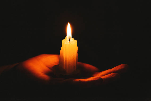 Burning candle on a female hand, dark background. Symbol of life, love and light