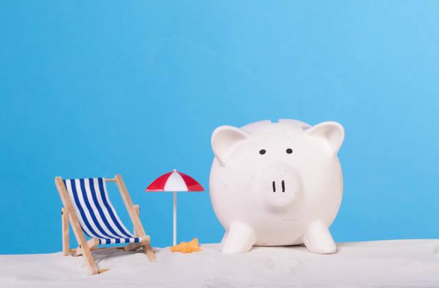 Sea chair with piggy bank on the sandy beach