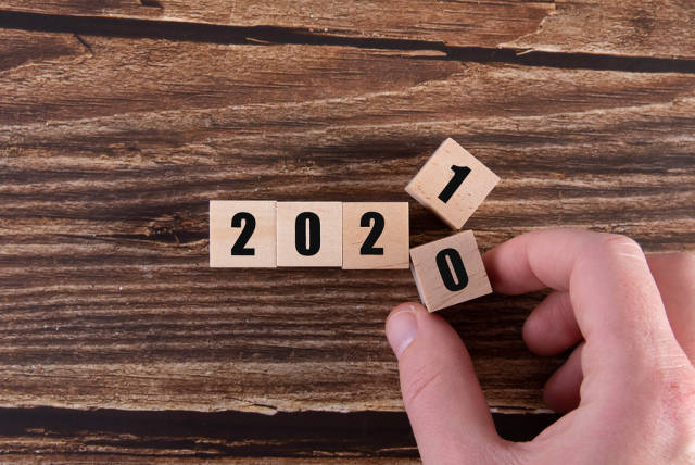 Hand flipping of wooden cubes block to change 2020 to 2021 year