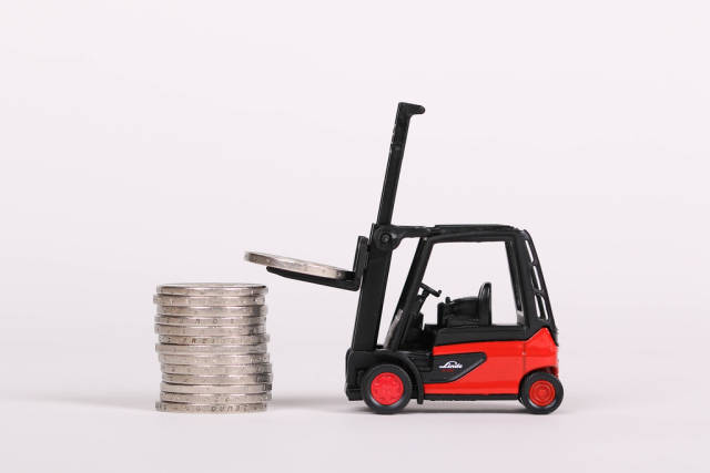 Red forklift lifting coins, business concept