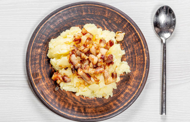 Mashed potatoes with fried onions and bacon in a plate on a white wooden background with a spoon. Top view