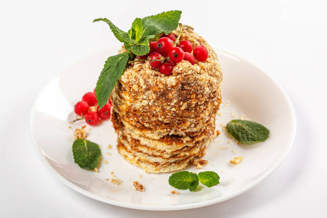 Honey cake with condensed milk, fresh mint leaves and red currant berries