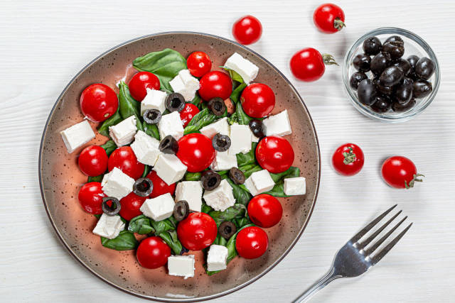 Top view salad with fresh vegetables and feta cheese on white wooden background