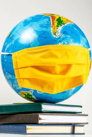 Globe in a yellow medical mask on a stack of books