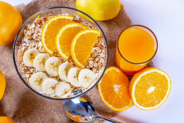 Ein Frühstück voller Vitamin C - Müsli mit Bananen und Orangen in einer Glasschüssel und Orangensaft in einem Glas auf Leinentuch