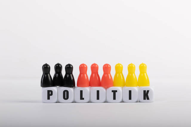 Pawn figurines with cubes and Politik text on white background