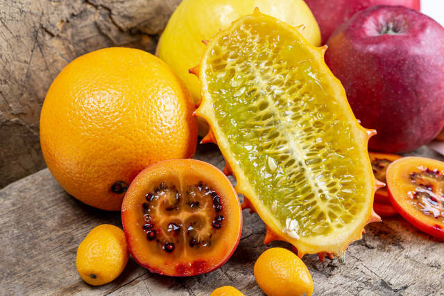 Fruit background with fresh citrus, quince, apples, sliced tamarillo and kiwano