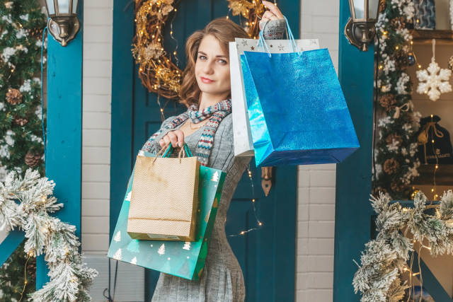 Smiling woman holding many packages in christmas interior