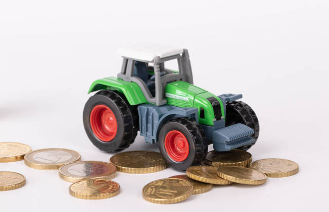 Tractor with coins on white background