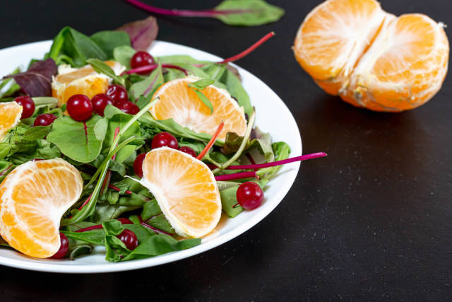 Diet salad with spinach, tangerine and cranberries on a black background
