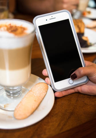 Hand holding a phone in a coffee shop