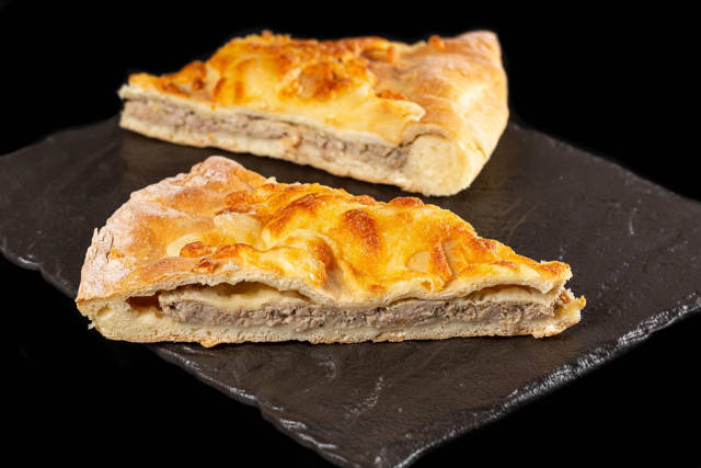 Sliced fresh khachapuri with cheese and minced meat