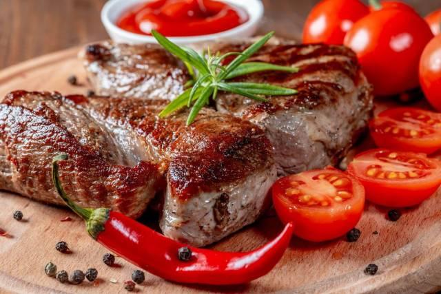 Saftig gebratene Steaks mit Cherrytomaten, Chili, Pfefferkörnern und Rosmarin auf Holzbrett
