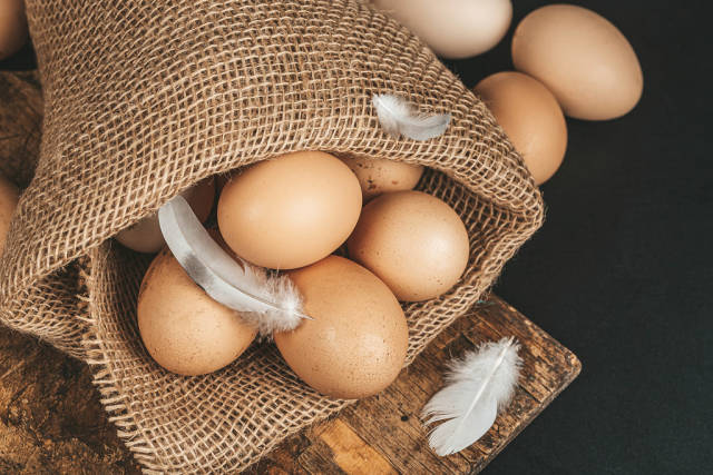 Eggs on burlap with feathers on a black background, top view