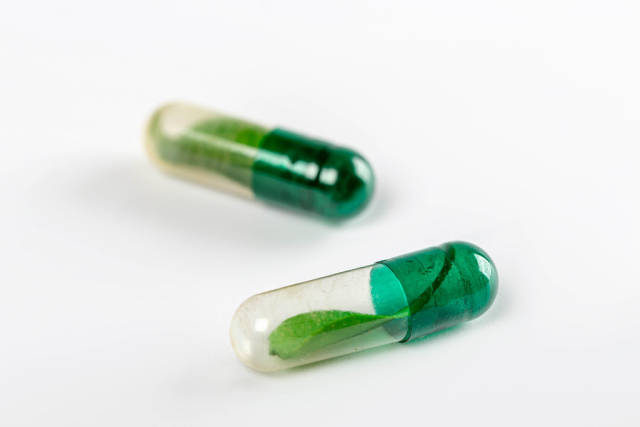 Two capsules with green leaves inside, natural preparations