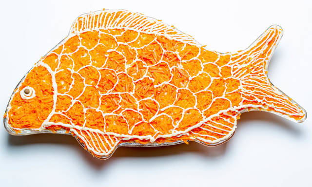 Salad layers in the shape of a fish on a white background