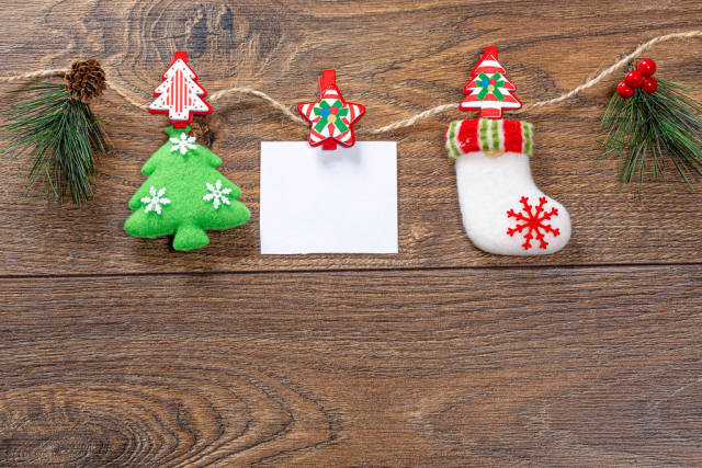 Christmas decor with thread on brown wooden background with free space