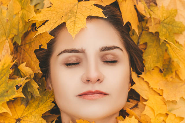 Girl with closed eyes on a background of fallen maple leaves