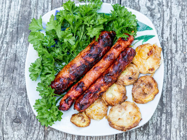 Top view of fried zucchini, grilled sausages and greens on old wooden background