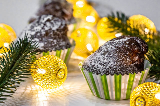 Chocolate cupcake with Christmas tree branches and a luminous garland