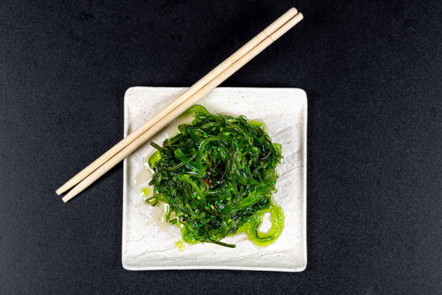 Top view, white plate with healthy seaweed salad on black background