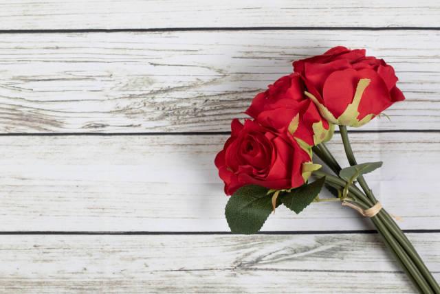 Drei zu Strauß gebundene Rosen auf weißem Holztisch