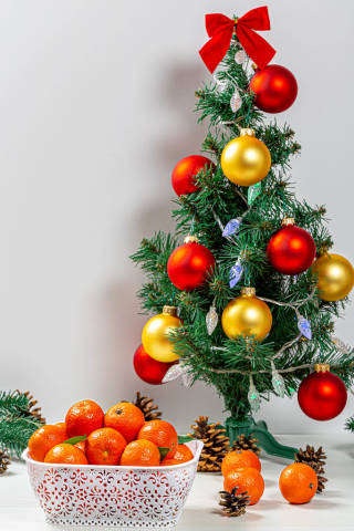 Christmas background with decorated Christmas tree and tangerines