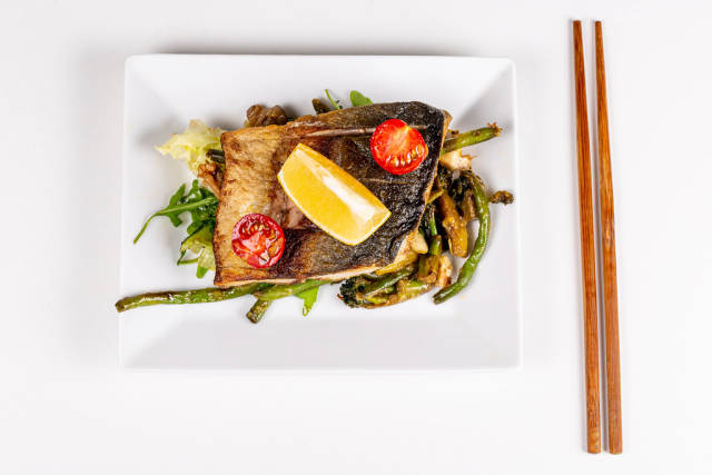 Top view of fried fish with vegetables on white plate with wooden chopsticks