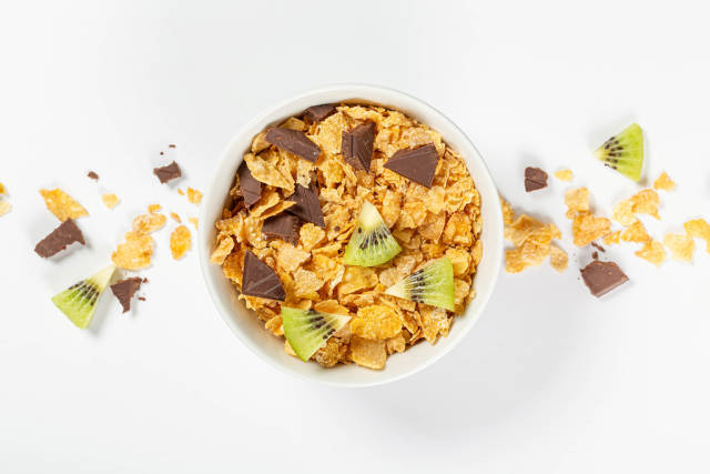 Ceramic bowl of corn flakes with kiwi and chocolate, top view