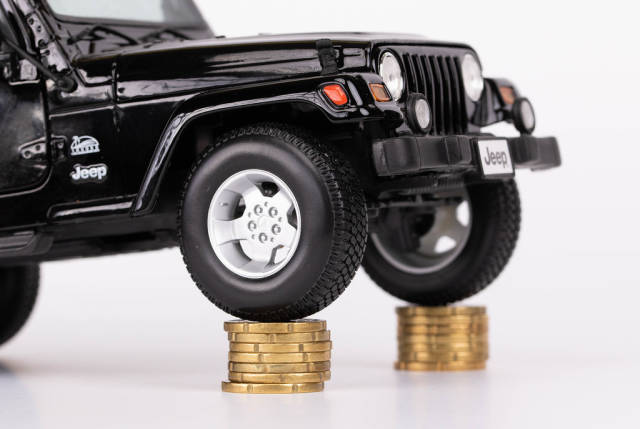 Black car on top of stack of coins