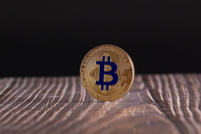 Golden Bitcoin coin on wooden table