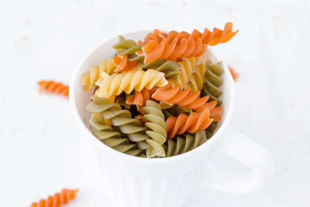 Uncooked three-colored pasta with spinach and tomato