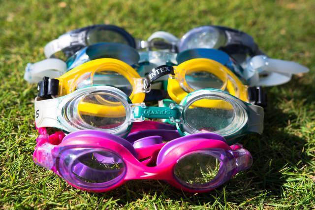 Schwimmbrillen verschiedener Farben auf dem Rasen