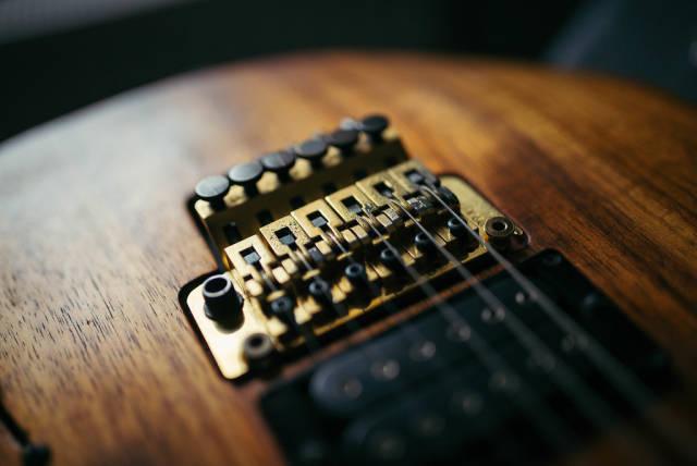 A golden Floyd Rose on an electric guitar