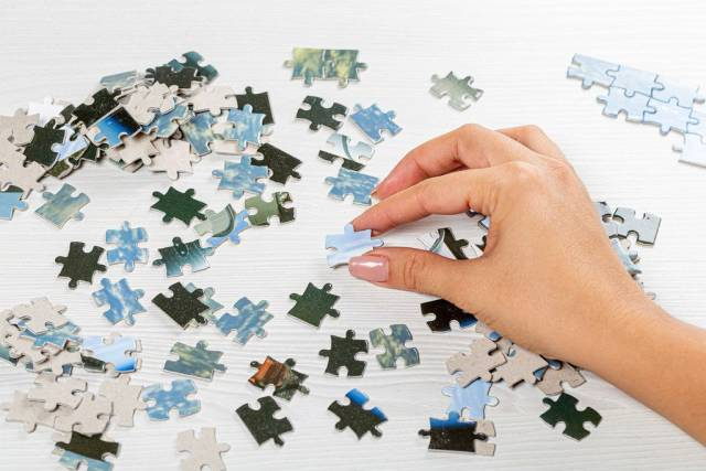Lots of puzzle pieces on the table and one in a womans hand (Flip 2019)