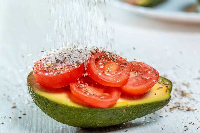 Sprinkle salt and spices on avocado stuffed with tomatoes