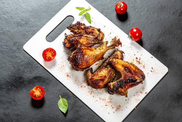 Top view pieces of baked chicken with tomatoes and Basil on a black background