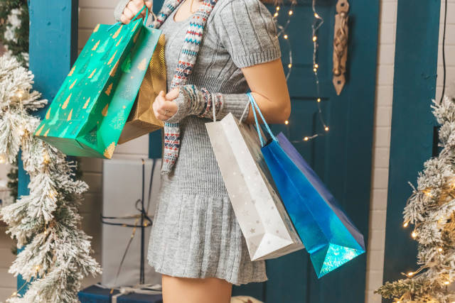 New Years shopping concept, girl with packages in hands