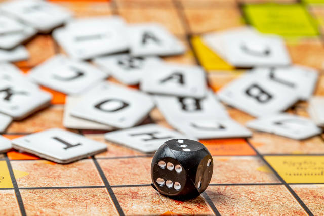 Close-up, black cube with numbers and letters behind it, the concept of the game of scrabble