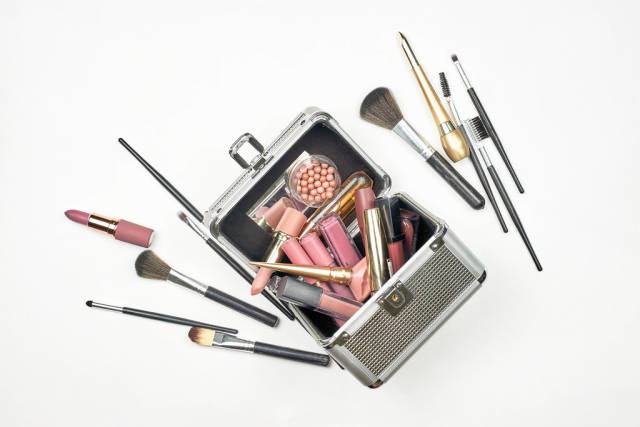 Cosmetic box with professional beauty tools and accessories on white background