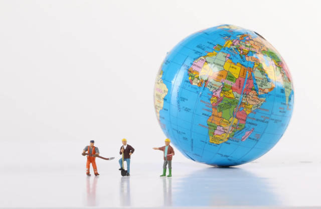 Miniature workers with globe on white background