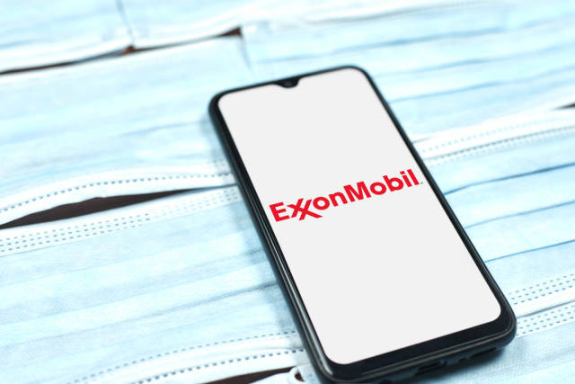 ExxonMobil logo on smartphone screen. American multinational oil and gas corporation during global pandemic