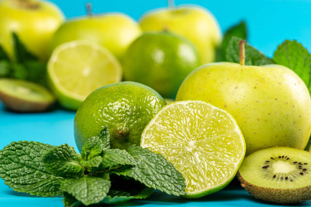 Close-up of lime, kiwi, apple and mint leaves on blue background