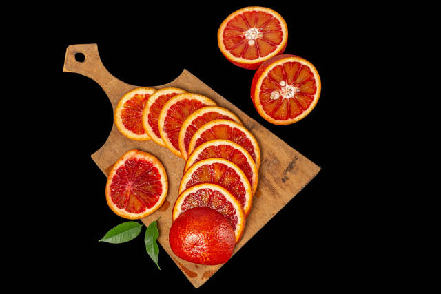 Ripe red oranges on dark background, top view